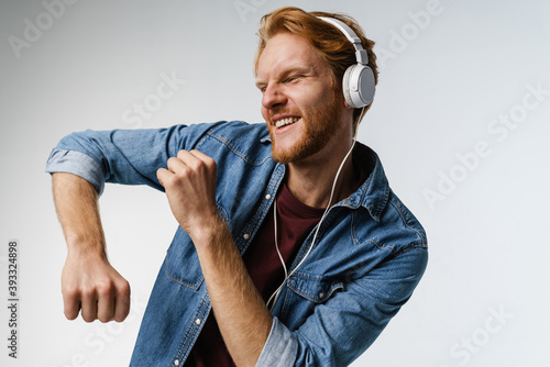 Fototapeta Happy handsome redhead guy in headphones singing and dancing