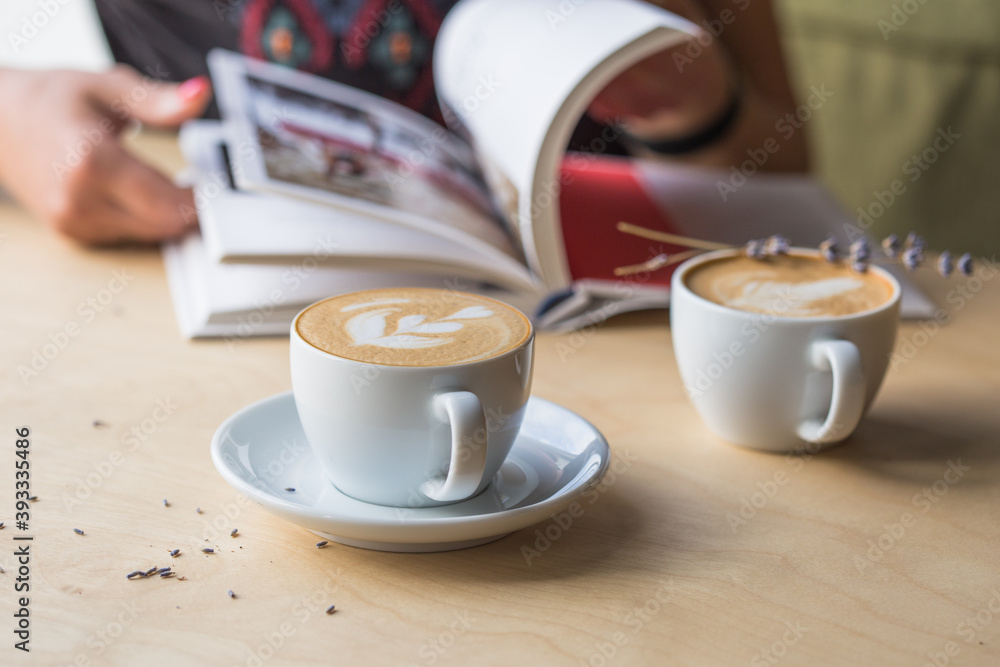Fototapeta Top view of hot cappuccino coffee in the cafe, Heart shape cream coffee in blue cup. Hands women holding hot coffee in cup Asian woman smelling and drinking hot coffee with feeling good in coffee shop