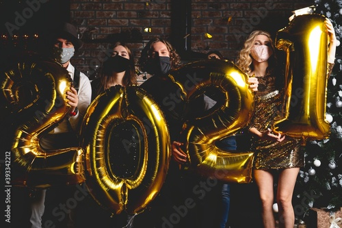 Corona virus pandemic. Party, people and new year holidays concept - women and men in protective medical mask celebrating new years eve 2021
