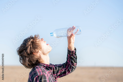 Fotografie, Obraz person in summer season feel thirsty and drink some water in desert