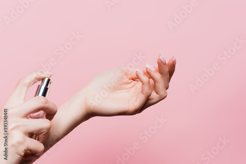 Fototapeta partial view of woman holding bottle and applying luxury perfume isolated on pink obraz
