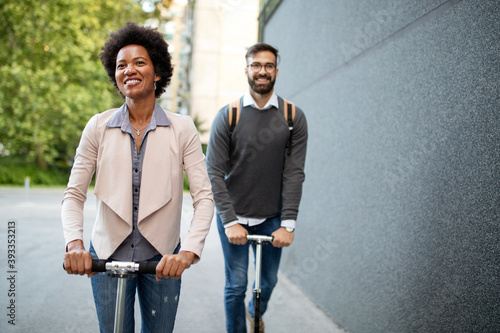Obraz Happy young couple enjoying together while riding electric scooters on city street - fototapety do salonu
