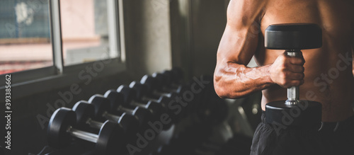 Canvastavla Muscular and strong athletic man exercising with dumbbells in the sport gym, wor