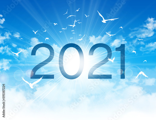 Year 2021 date number, high in blue sky with the sunrise and birds flight. New year Greeting card.