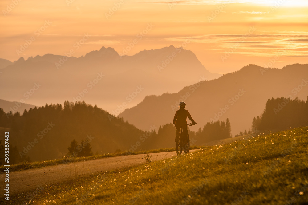 Fototapeta active woman riding her electric mountain bike at sunset in front of the awesome silhouette of Mount Saentis, Appenzell switzerland