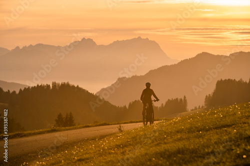 Fototapeta premium active woman riding her electric mountain bike at sunset in front of the awesome silhouette of Mount Saentis, Appenzell switzerland