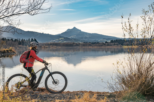Tableau sur Toile nice senior woman with electric mountain bike enjoying the view over autumnal la