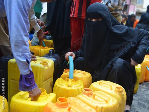 Fotomural A Yemeni woman fetching water due to the water crisis in Taiz