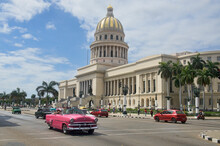 Classic Cars Drive Past The Capitolio Building, Havana, Cuba