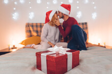 Couple In Love Kissing Celebrating Christmas Time Together - Boyfriend And Girlfriend Opening Presents At Home - Winter Holiday X Mas Concept