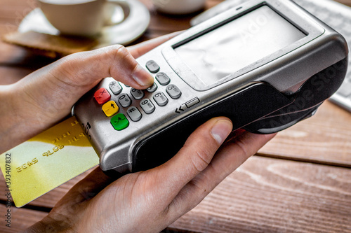Foto Payment by card in cafe with terminal and keyboard on wooden background