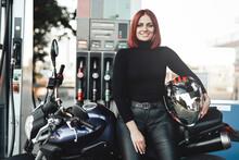 A Joyful Female Biker Enjoying Her Motorcycle. A Modern Bike And Its Female Owner In The Refueling. Retro Styled Photo.