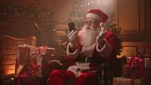 Santa Claus Is Communicating By Video Call At Smartphone, Sitting In His Residence At Christmas Night