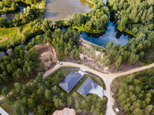 Top Drone View Of Green Forest In Countryside Village. Construction Site Between Trees In Marshland. Latvian Nature.