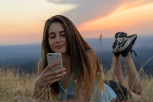 Smiling Young Woman Using Cell Phone Lying In Grass During Sunset