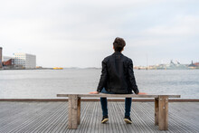 Denmark, Copenhagen, Rear View Of Young Man Sitting On A Bench At The Waterfront