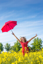 Carefree Woman With Arms Raised Holding Umbrella While Standing Amidst Oilseed Rapes