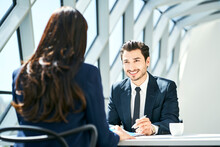 Smiling Businessman Looking At Businesswoman In Modern Office