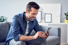Smiling Man Sitting On Sofa Using Cell Phone