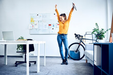Happy Young Businesswoman Cheering In Office