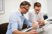 Two Businessmen Examining Solar Panel On Desk In Office