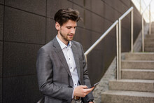 Businessman Using Cell Phone On Stairs