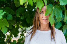Mature Woman With Blue Eyes Standing Under Green Leaves At Back Yard