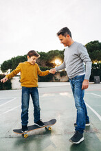 Father Assisting Son Riding Skateboard