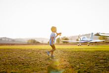 Cute Little Boy Playing With Toy Plane While Standing At Airfield On Sunny Day