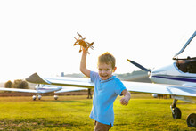Cute Little Boy Playing With Toy Plane While Standing At Airfield