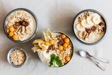 Three Bowls Of Porridge With Oats, Flax Seed, Winter Cherries And Bananas