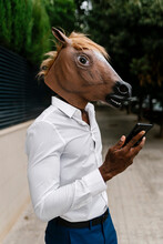 Male Entrepreneur Wearing Horse Mask While Holding Smart Phone In City