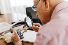 Retired Senior Male Looking Through Magnifying Glass At Mineral