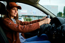 Young Woman Smiling While Driving Car In City