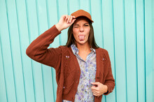 Woman Teasing With Sticking Tongue Out While Standing Against Metal Door