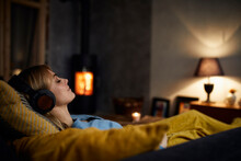 Smiling Woman Listening Music With Headphones On Couch At Home In The Evening