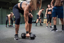 Woman Picking Dumbbell With Pe...