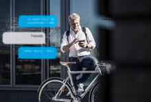 Smiling Mature Businessman With Bicycle Using Cell Phone For Messaging In The City