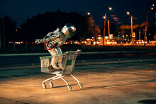 Spaceman In The City At Night On Parking Lot Inside Shopping Cart
