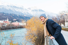 Austria, Innsbruck, Portrait Of Smiling Young Man Looking At Distance