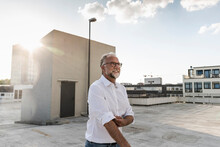 Mature Man Standing On Roof Of...