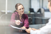 Woman Showing Contract To Client At Desk