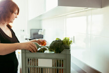 Woman Removing Vegetable And Fruit From Basket While Standing At Kitchen