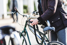 Businessman Locking Bicycle In...