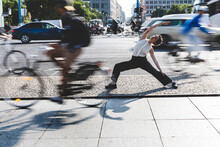 Young Businesswoman Practising Yoga In The City At Rush Hour, Berlin, Germany