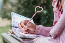 Close-up Of Young Woman Writing In Diary At Park