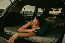 Tired Woman Sleeping In Car Trunk At Dusk