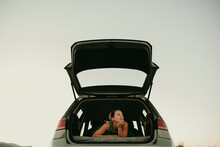 Thoughtful Woman Looking Away While Lying In Car Trunk Against Clear Sky