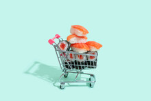Fresh Salmon Sushi Nigiri Stacked In Small Shopping Cart Against Mint Green Background