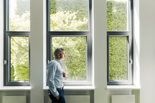 Businessman With Hands In Pockets Looking Through Window While Standing At Office